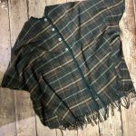 A short green button up cape with tassels